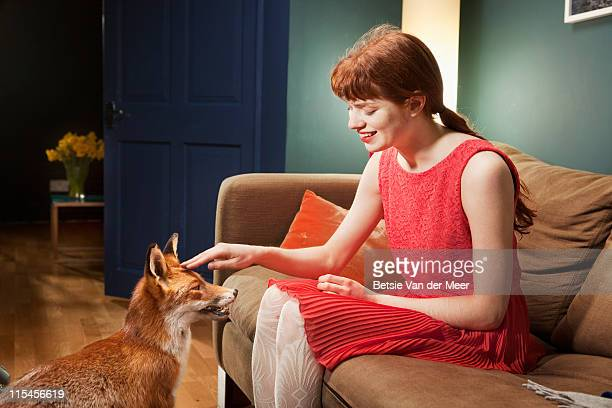 Woman stroking fox, while sitting on sofa.