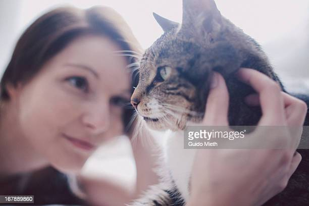 Woman stroking her cat.