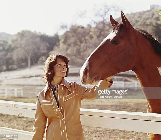 Woman stroking horse beside fence