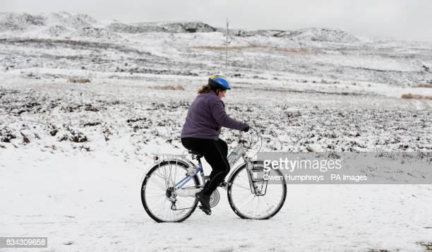 A woman struggles to cycle through the snow near Stanhope in Co Durham today more snow is forecast for the rest of the weekend