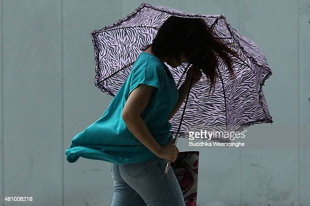 A woman struggles to hold an umbrella against strong wind and rain delivered by typhoon Nangka on July 17 2015 in Himeji Japan As Typhoon Nangka made...