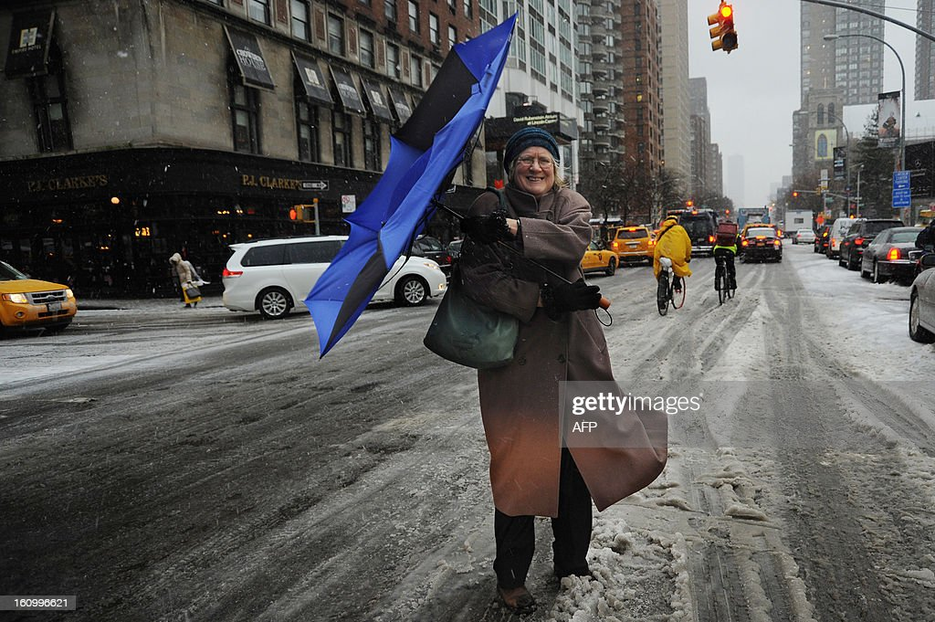 A woman struggles with her umbrella in New York on February 8, 2013 during a storm affecting the northeast US. The storm was forecast to bring the heaviest snow to the densely-populated northeast corridor so far this winter, threatening power and transport links for tens of millions of people and the major cities of Boston and New York. New York and other regional airports saw more than 4,500 cancellations ahead of what the National Weather Service called 'a major winter storm with blizzard conditions' along most of the region's coastline.