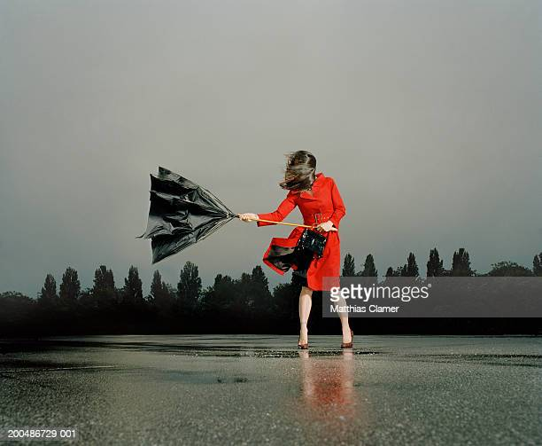 Woman struggling with broken umbrella in rain