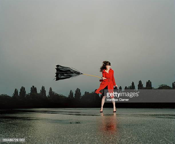 Woman struggling with broken umbrella in wind and rain