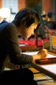 A woman studies jananese calligraphy