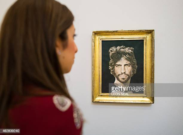 A woman studies 'Portrait of Gerard Pique as Apollo del Belvedere' by Francesco Vezzoli with an estimate of £3000040 during a press preview in...