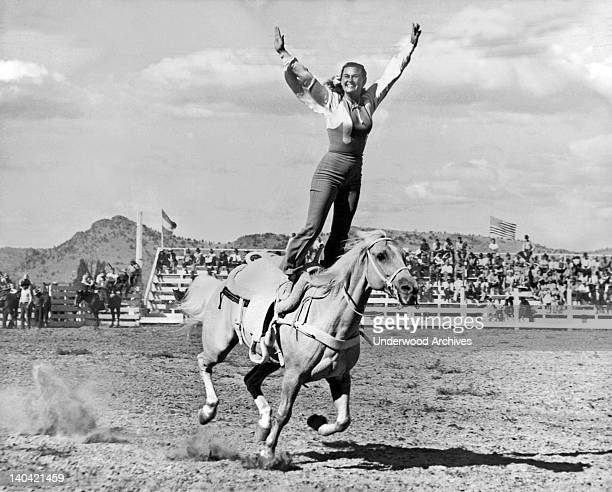 A woman stunt rider does a 'Roman Stand' on a fast running palomino quarter horse Oregon circa 1937