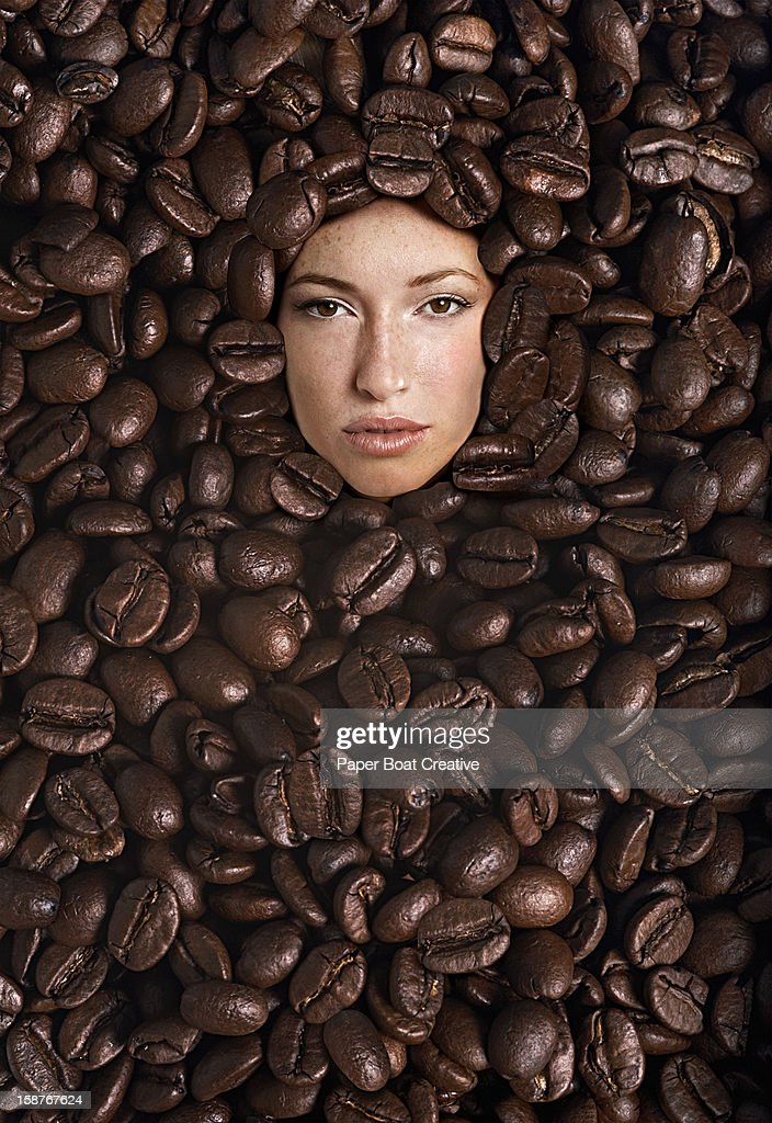 Woman submersed in a bunch of giant coffee beans : Stock Photo