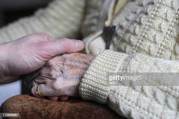 A woman suffering from Alzheimer's desease holds the hand of a relative on March 18 2011 in a retirement house in Angervilliers eastern France AFP...