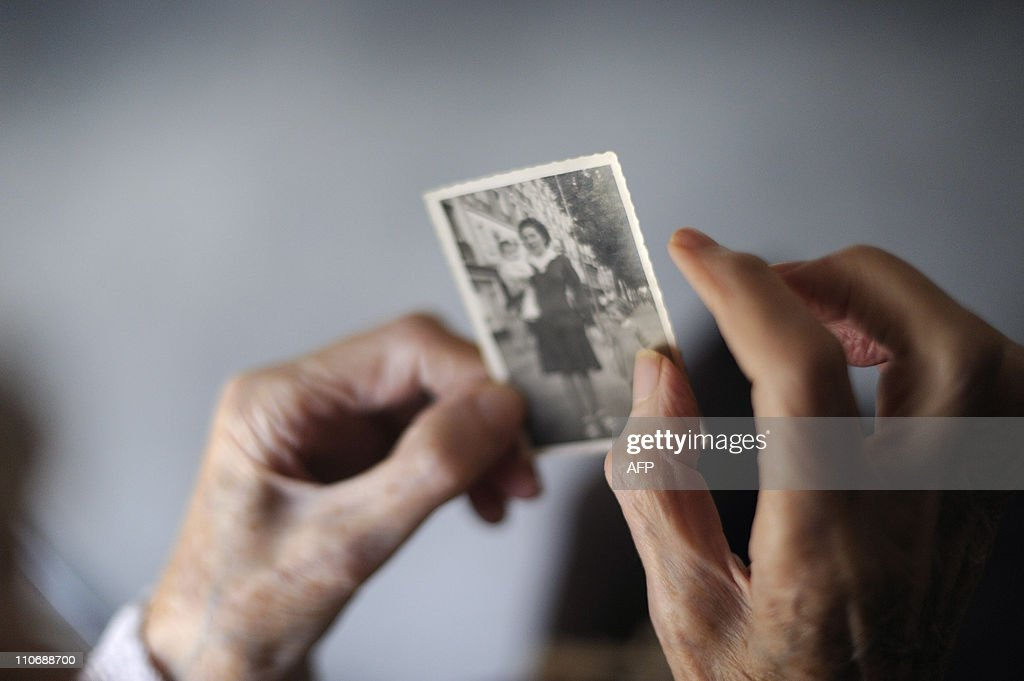 A woman, suffering from Alzheimer's desease, looks at an old picture of herself on March 18, 2011 in a retirement house in Angervilliers, eastern France.
