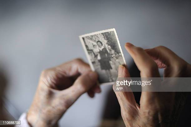 A woman suffering from Alzheimer's desease looks at an old picture of herself on March 18 2011 in a retirement house in Angervilliers eastern France...