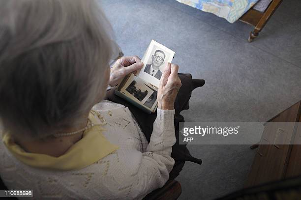 A woman suffering from Alzheimer's desease looks at an old picture on March 18 2011 in a retirement house in Angervilliers eastern France AFP PHOTO /...