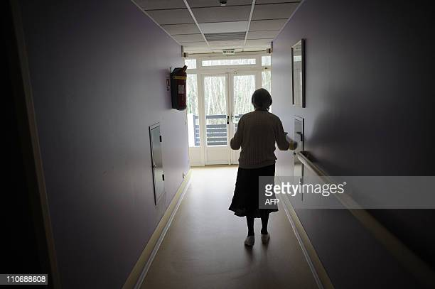 A woman suffering from Alzheimer's desease walks in a corridor on March 18 2011 in a retirement house in Angervilliers eastern France AFP PHOTO /...
