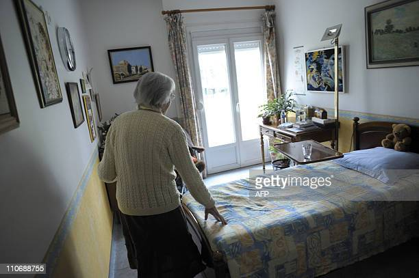 A woman suffering from Alzheimer's desease walks in her room on March 18 2011 in a retirement house in Angervilliers eastern France AFP PHOTO /...