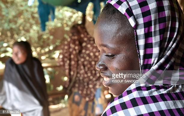 A woman suffering from obstetric fistula smiles as she goes about with her daily life in the health centre of the Non Governmental Organisation DIMOL...