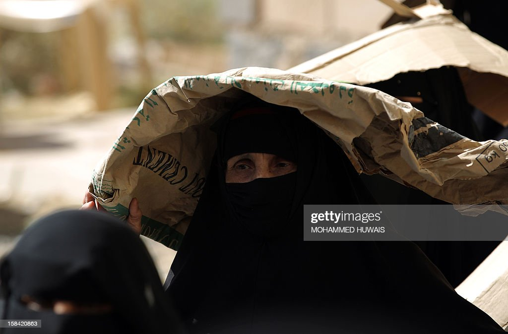 A woman suffering from problems with her eyes holds an empty cement bag over her head to protect her from the sun as she waits to be seen by optician from a Yemeni charity specializing in eye treatment on the outskirts of Sanaa on December 16, 2012. So far only 43 percent of $455 million earlier asked for by the United Nations and other organisations has been received for humanitarian aid for Yemen. AFP PHOTO/ MOHAMMED HUWAIS