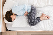 Young Woman With Stomach Ache Lying On Bed
