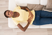 Young African Woman Lying On Sofa Suffering From Stomach Ache