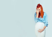 Pre partum depression. Beautiful young woman stressed waiting for baby and having health problems looking tired and exhausted isolated on light blue. Mixed race model, latin hispanic irish woman