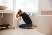 Woman Suffering With Morning Sickness In Bathroom At Home