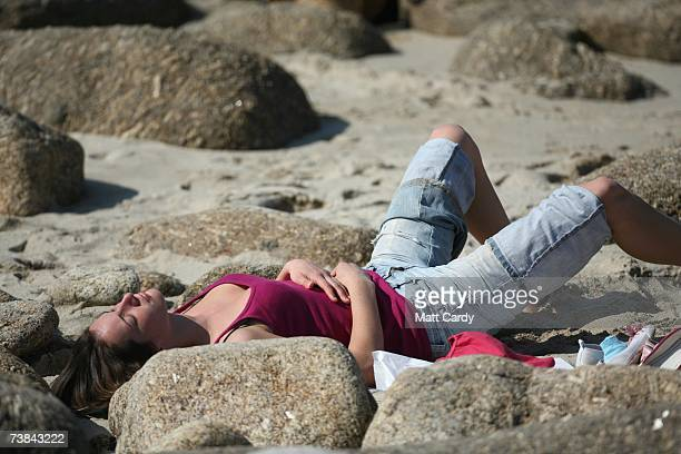 A woman sunbathes as she enjoys the holiday sunshine in Sennen on April 9 2007 in Cornwall England The UK's Easter weekend was blessed with good...