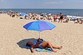 A woman sunbathes at Rockaway Beach on July 26 2016 in New York City A heat wave continues with temperatures expected to stay in the 90's across most...