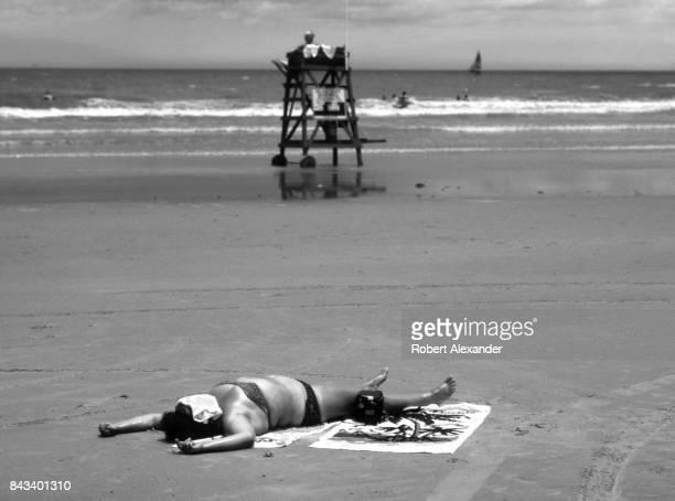 A woman sunbathes on the beach near a lifeguard stand in Daytona Beach Florida in 1983