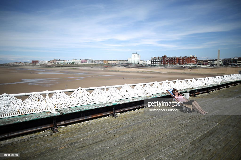 A woman sunbathes on the North Pier as sunshine and warm weather greets visitors to Blackpool Promenade on June 3, 2013 in Blackpool, England. After one of the coldest Springs on record, sunshine and fine weather is being forcast all across Britain this week with termperatures as high as 25C in some areas.