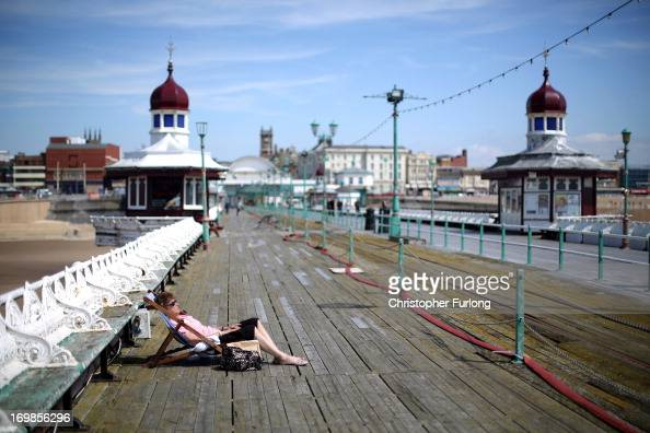 A woman sunbathes on the North Pier as sunshine and warm weather greets visitors to Blackpool Promenade on June 3 2013 in Blackpool England After one...