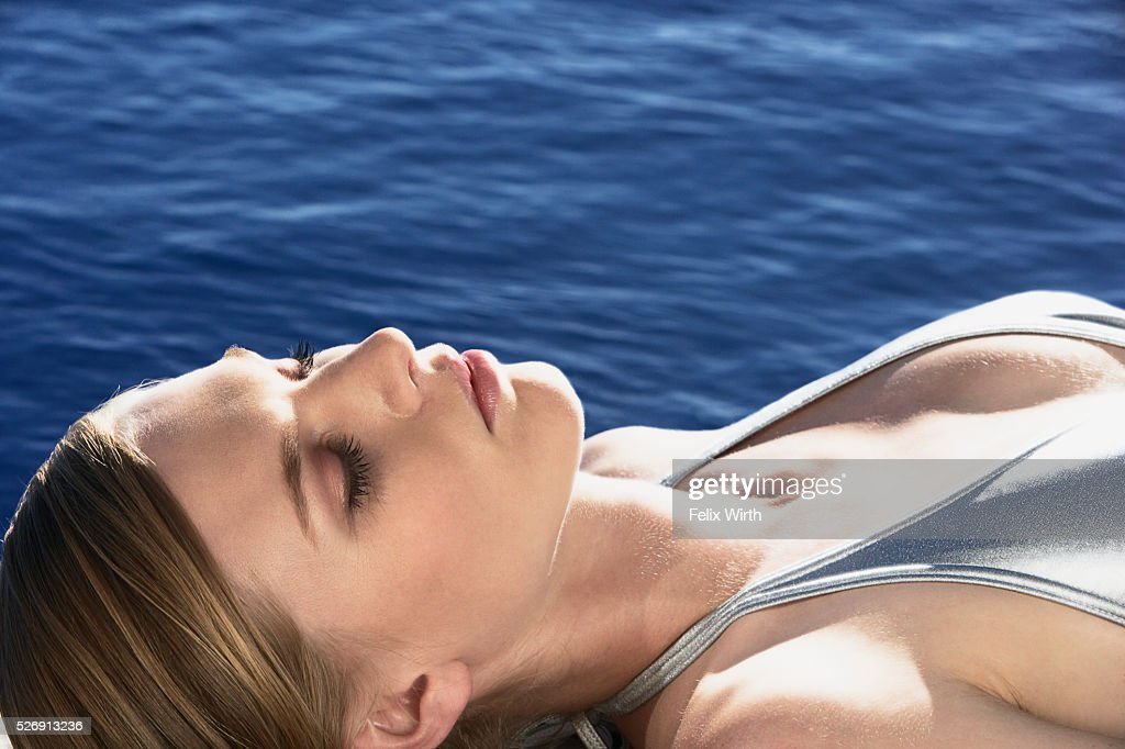 Woman sunbathing by pool : Stock Photo