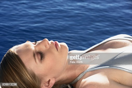 Woman sunbathing by pool : Foto de stock
