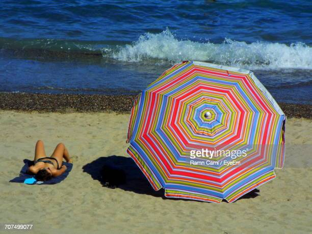 Woman Sunbathing By Striped Colorful Parasol On Shore At Beach