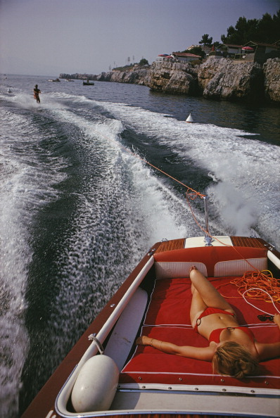 A woman sunbathing in a motorboat as it tows a waterskiier in the sea off the Hotel du CapEdenRoc in Antibes on the French Riviera August 1969