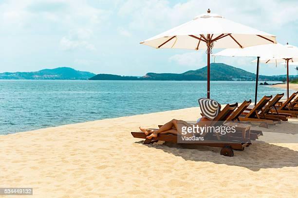 Femme au soleil sur une chaise de plage