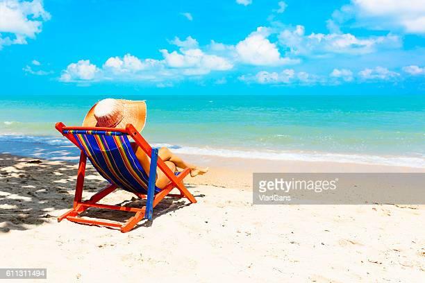 Frau Sonnenbaden im Strand-Stuhl