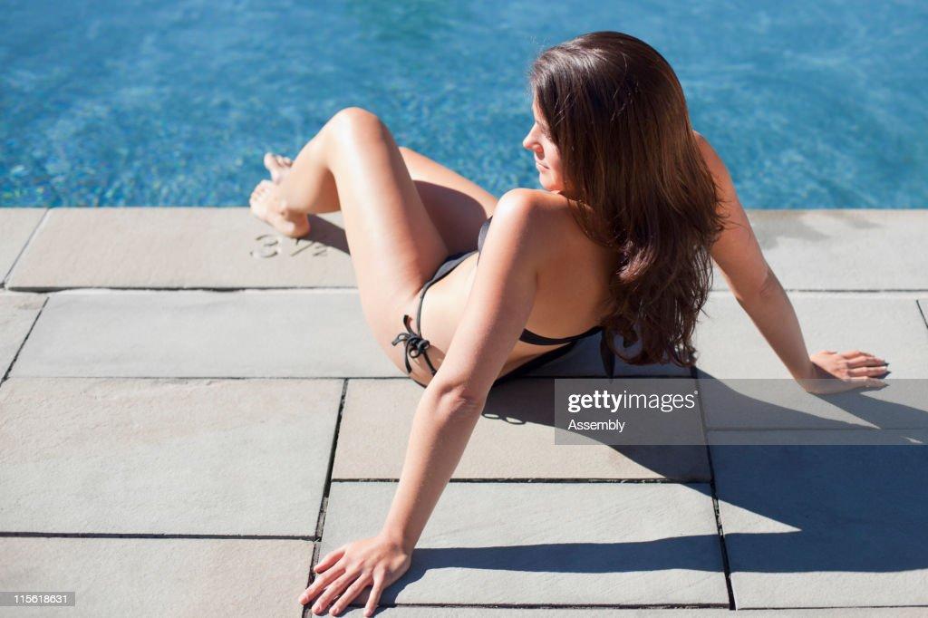 Woman sunbathing near swimming pool : Stock Photo