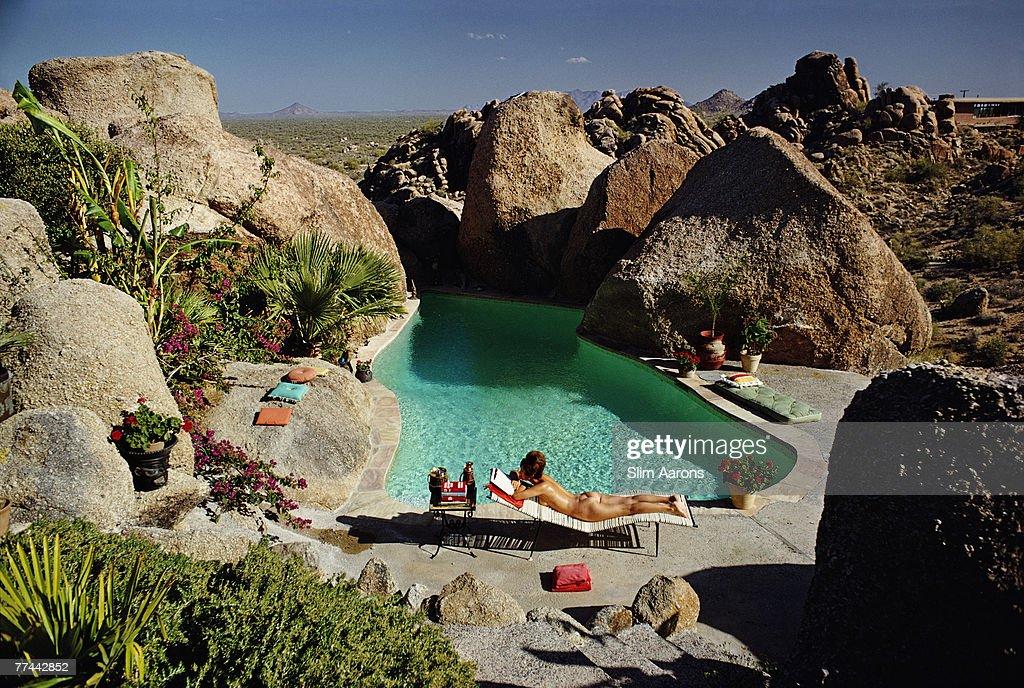 A woman sunbathing nude by Tom Darlingtons pool in