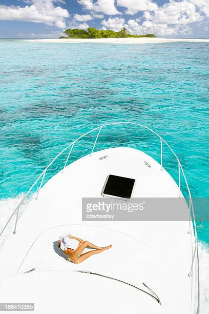 woman sunbathing on a luxury yacht approaching deserted island