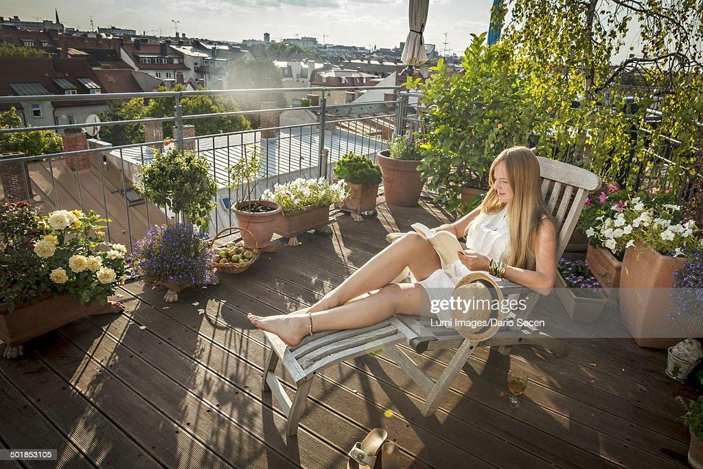 Woman Sunbathing On Balcony, Munich, Bavaria, Germany, Europe