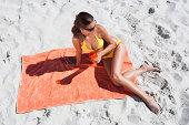 Woman sunbathing on beach towel in sand with beverage