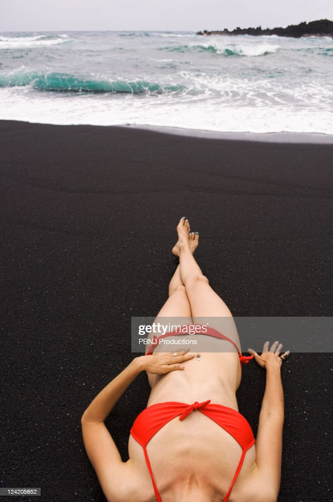 Woman sunbathing on black sand beach : Stock Photo