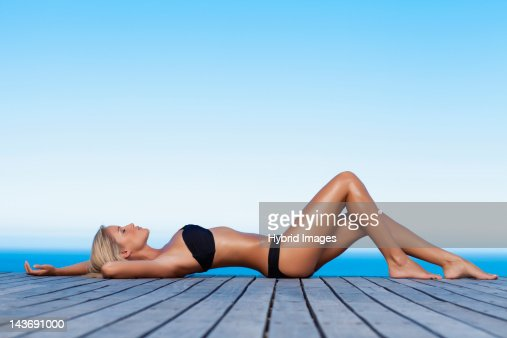 Woman sunbathing on wooden pier : Bildbanksbilder