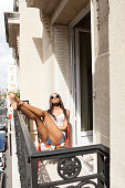 Woman sunning on balcony, Paris, France