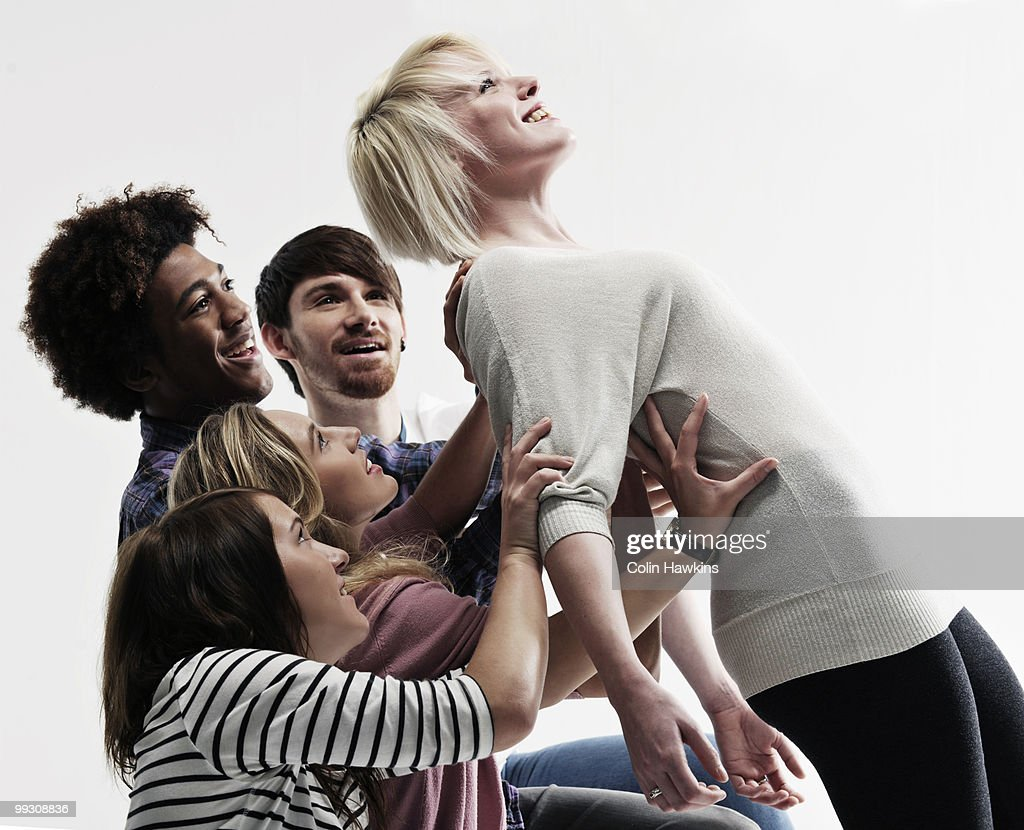 Woman supported by 4 young people : Stock Photo