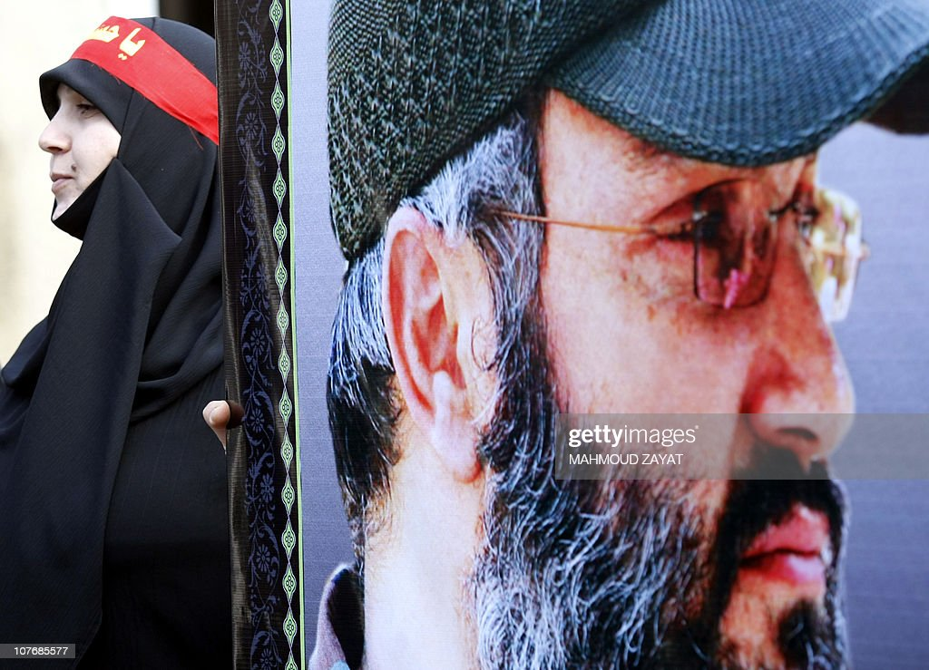 A woman supporter of the Shiite Muslim Hezbollah movement holds onto an image of the movement's slain commander Imad Mughniyeh during a Hezbollah...