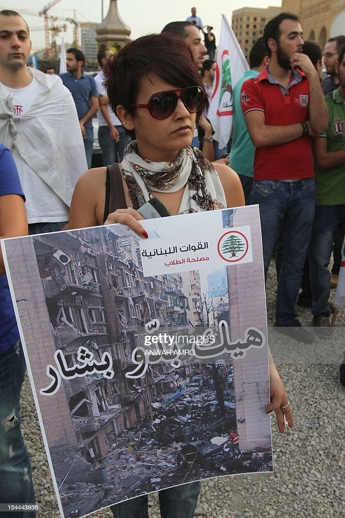 A woman supporters of the March 14th anti-Syrian opposition coalition holds up a poster that reads in Arabic, 'This is what Bashar wants' refering to Syrian President Bashar al-Assad, takes part in a protest a day after the assassination of Internal Security Forces (ISF) intelligence chief General Wissam al-Hassan in Martyrs' Square in downtown Beirut, on October 20, 2012. Lebanon was reeling the day after Hassan was killed in a bombing that was blamed on Syria and also raised fears the country is being sucked into the war ravaging its neighbour.