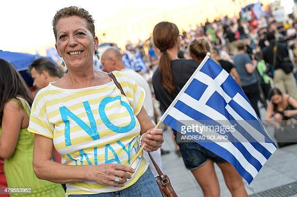 A woman supporting a 'No' vote in the Greek referendum holds a Greek national flag as she celebrates at Syntagma Square in Athens on July 5 2015...
