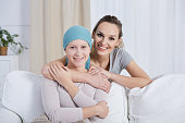 Smiling young woman hugging and supporting her ill sister