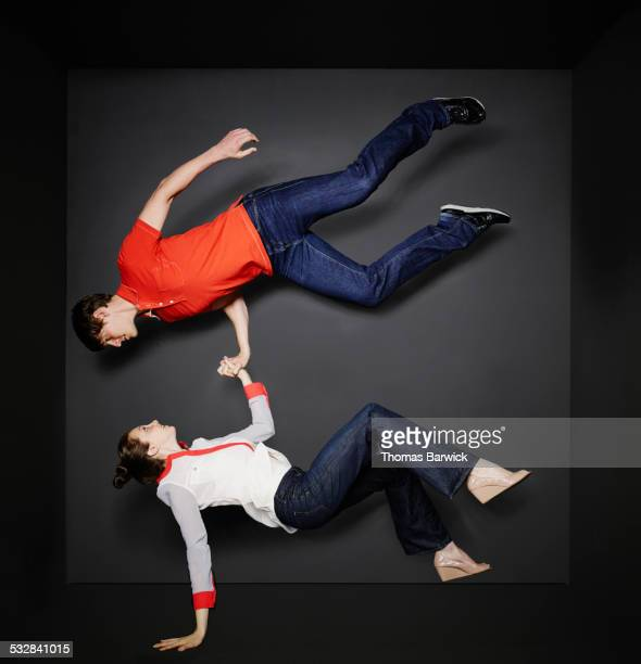 Woman supporting man in mid air with one hand