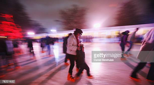 A woman supports a child as they ice skate at the Winter Wonderland in Hyde Park on December 1 2007 in London England The Winter Wonderland is a new...